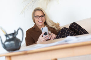 Personal branding headshot of a woman working at a desk with phone