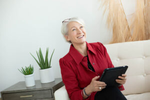 Casual headshot of a woman holding a laptop and looking up through the window